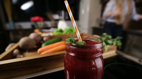 Jar of fresh beetroot smoothie with striped straw Footage
