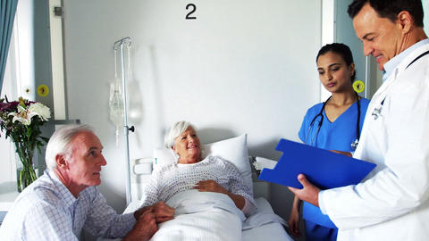 Doctor discussing report with senior couple Footage