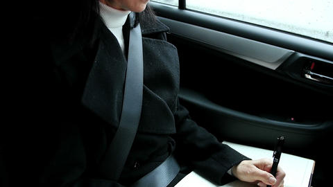 Woman sitting in car and writing on diary Footage