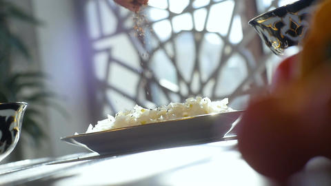 Macro Cook Pours Salt Over Rice Meat Cubes on Plate on Table Footage