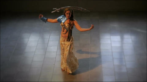 A millennial woman dressed in traditional ethnic clothing dancing with a sword o Footage