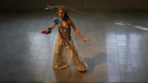 An attractive woman in an arabic costume balances a sword on her head while danc Footage