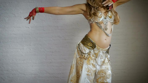 A seductive belly dancer shakes her hips while wearing a black headpiece in slow Footage