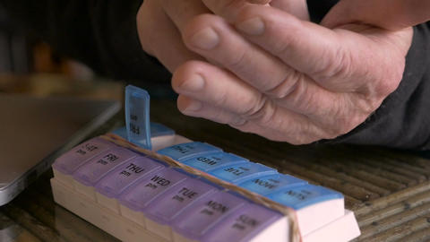 Close up of an elderly man's hands filling his daily pill planner with medicatio Live Action