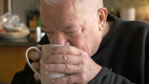 An attractive aging senior man drinking a cup of hot coffee or tea in slow motio Footage
