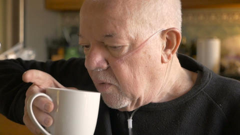 A senior man drinking coffee while wearing oxygen supplementation in slowmo Footage