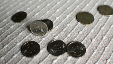 Coins fall and bounce onto a texture surface Footage