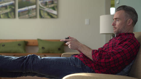 Man intently playing a video game on a couch Footage