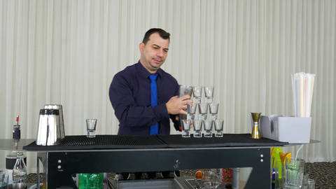 Bartender pouring drinks from shaker into tower shots Footage