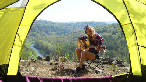Woman Sitting On Camping Chair And Playing Guitar Footage