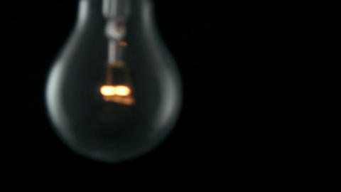 Light bulb swinging and flickering. Slow motion Footage