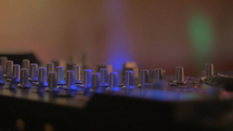 Dolly shot of knobs on a mixing board or DJ controller at a nightclub with flash Footage