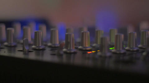 Slider shot of knobs of a DJ mixing board and colored meter lights moving Footage