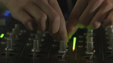Close up of two hands adjusting knobs and pushing buttons a DJ mixing board Footage