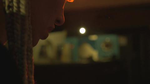 Side profile of a beautiful woman DJ wearing headphones dancing in red light in  Footage