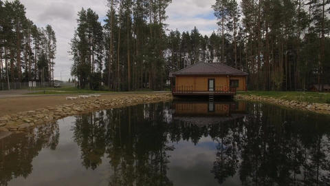 Camera Moves Over Lake Surface to Wooden House Filmmaterial