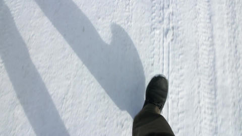 person walks on a snow-covered road overhead shot Footage