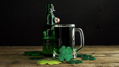 Green beer, bottle and shamrocks on wooden table for st patricks Live Action