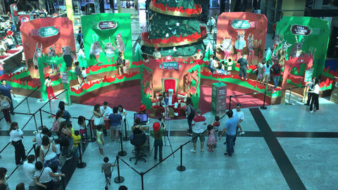 Kids taking photos with Santa Claus in a mall Footage
