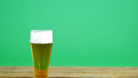 Pint of beer on wooden table with green background for st patricks Live Action