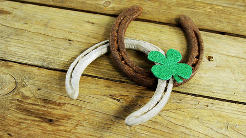 Horse shoes and shamrock side view on wooden table for st patricks Live Action