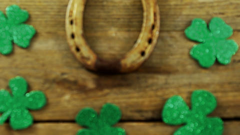 Horse shoe surrounded by shamrocks on wooden table for st patricks Live Action