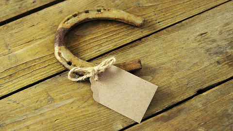 Horse shoe and tag on wooden background for st patricks Live Action
