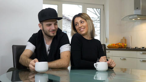 Happy loving couple teasing and joking while drinking coffee in their kitchen at Footage