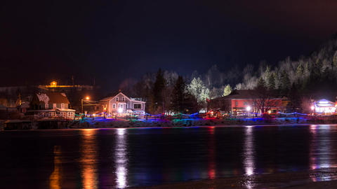 Time lapse of small town at night during the holidays with river in foreground Footage