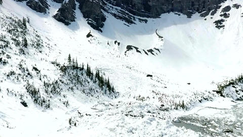 Aerial: Flying over frozen lake and avalanche debris Footage