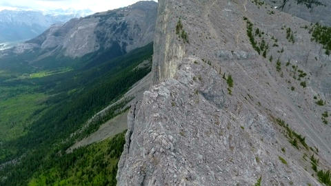 Aerial: Orbit around vertical mountain face with hikers climbing Footage