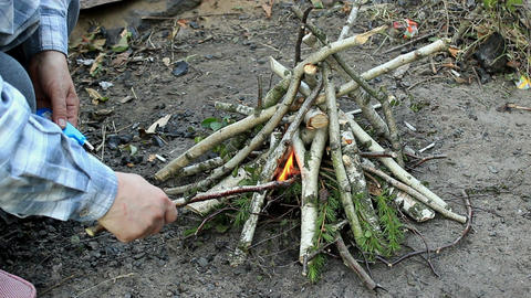 Adjusting the fire with a stick Footage
