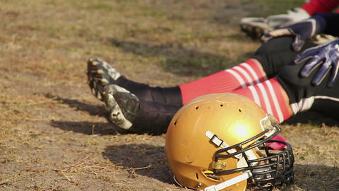 American football player sitting on the pitch, having rest after hard training Footage