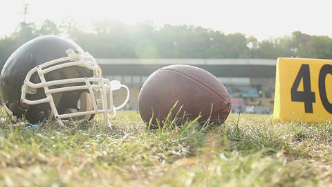 American football helmet and ball lying on pitch, summer camp sport activities Footage