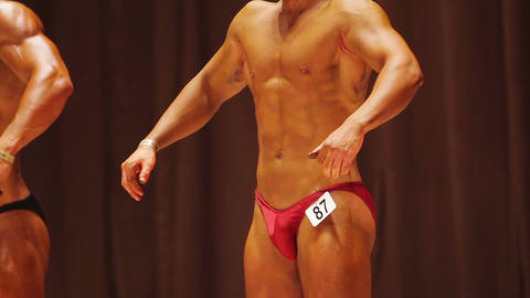 Bodybuilding competition, front lat spread pose, strong male posing on stage Footage
