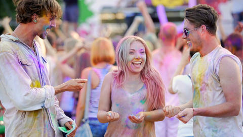 Cheerful young people throwing colorful powder in air, dancing at festival Footage