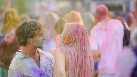 Happy couple hugging, flirting and dancing in crowd at outdoor color festival Live Action