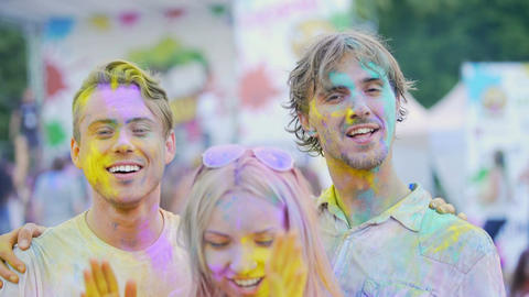 Excited young friends having fun at color festival, smiling and posing to camera Footage