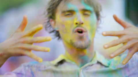 Crazy dance performed by excited cheerful man throwing colored powder in air Footage