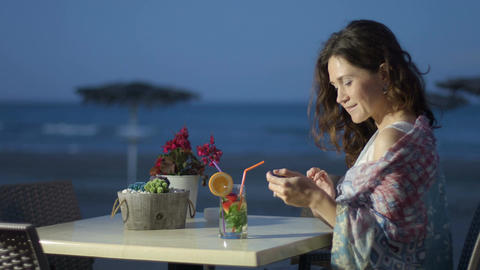 Beautiful young lady using mobile phone at outdoor restaurant, looking to camera Footage