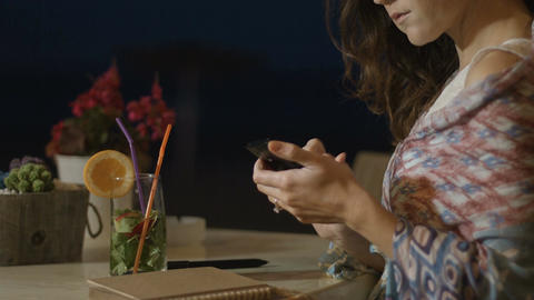 Smiling young female typing message on smartphone, chatting online at restaurant Footage