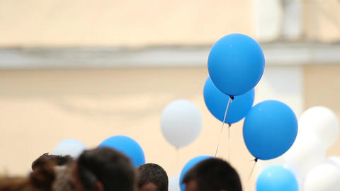 People holding colorful balloons to congratulate students at graduation ceremony Footage
