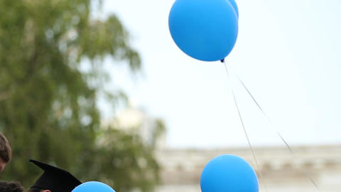 Happy graduates holding balloons before releasing them, students' tradition Footage