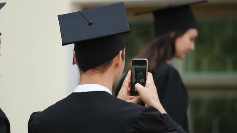 Male student taking many pictures of friends, graduation ceremony, happy youth Live Action