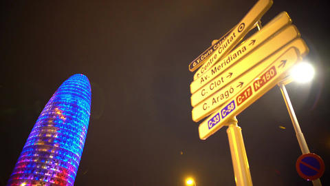 Torre Agbar illuminated at night, Barcelona landmark, street names on road signs Footage