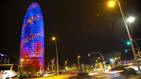 Many cars rushing by illuminated Torre Agbar, hectic night city life, time-lapse Live Action