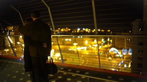 Happy married couple hugging on top of skyscraper, looking at night city lights Footage
