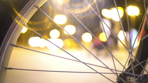 Night city life, defocused people walking street, view through bicycle wheel Footage