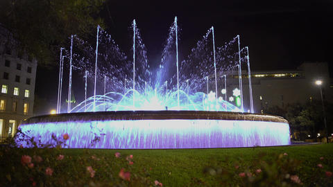 Fantastic dancing fountain, illuminated water streams moving to music at night Footage