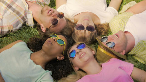 Happy people lying in circle on grass in park and singing songs, having fun Footage